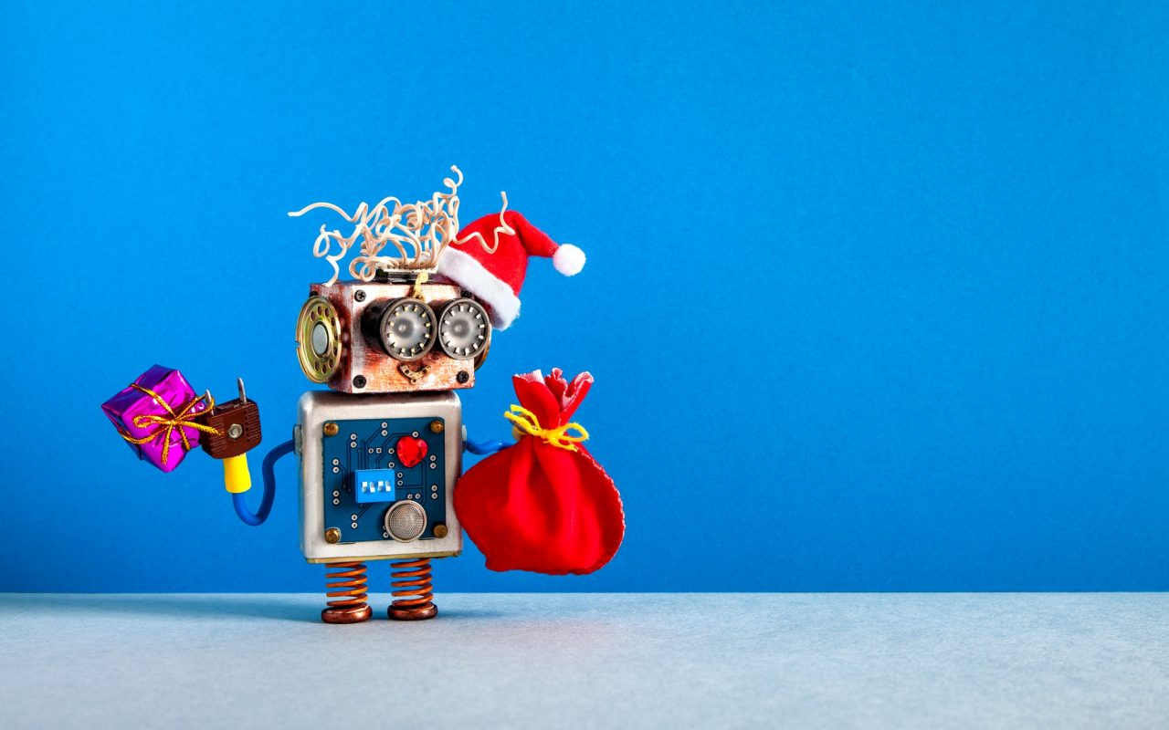 Christmas background. Funny Santa hat robot, holds box present and a red bag of gifts.
